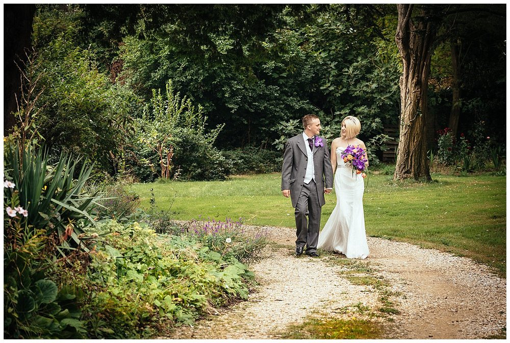 Bride and Groom take a stroll in the church Gardens