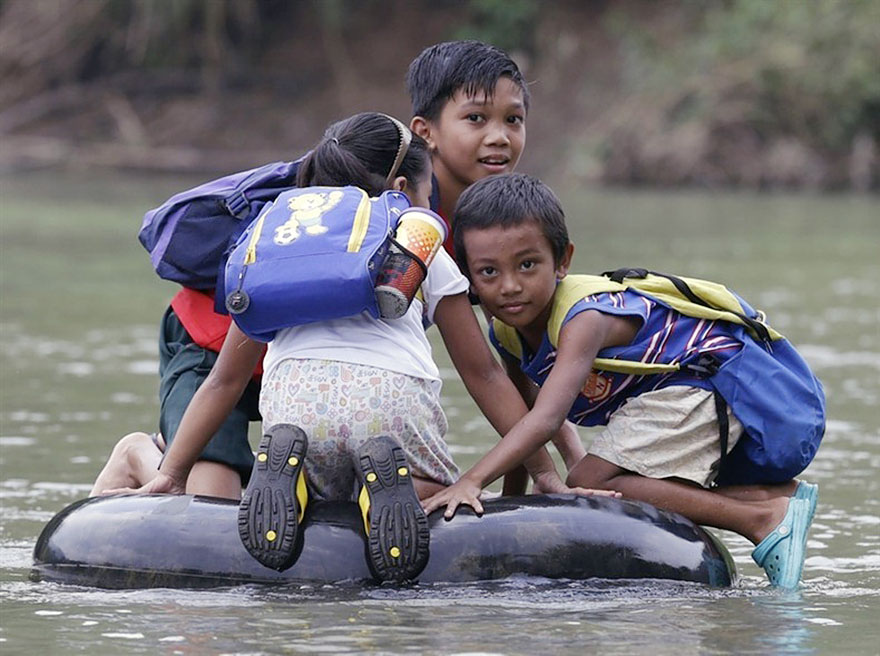 Elementary School Students Crossing A River On Inflated Tire Tubes, Rizal Province, Philippines