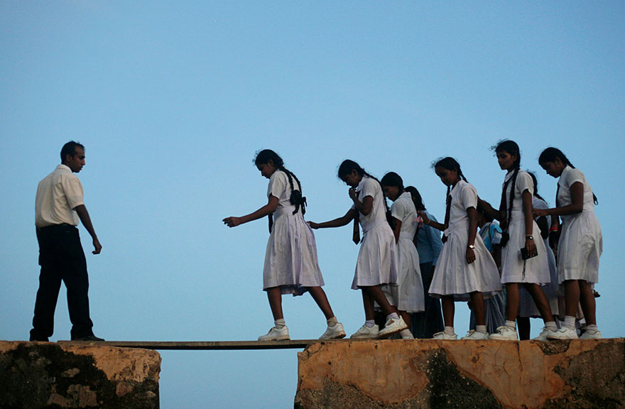 School Girls Walking Across A Plank On The Wall Of The 16th Century Galle Fort In Sri Lanka