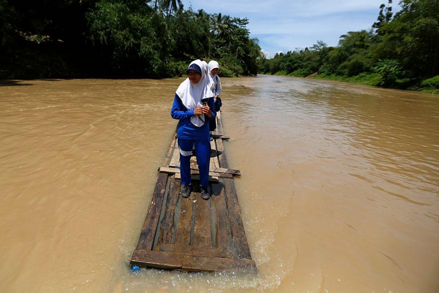 Students Crossing Ciherang River On A Makeshift Bamboo Raft, Cilangkap Village, Indonesia