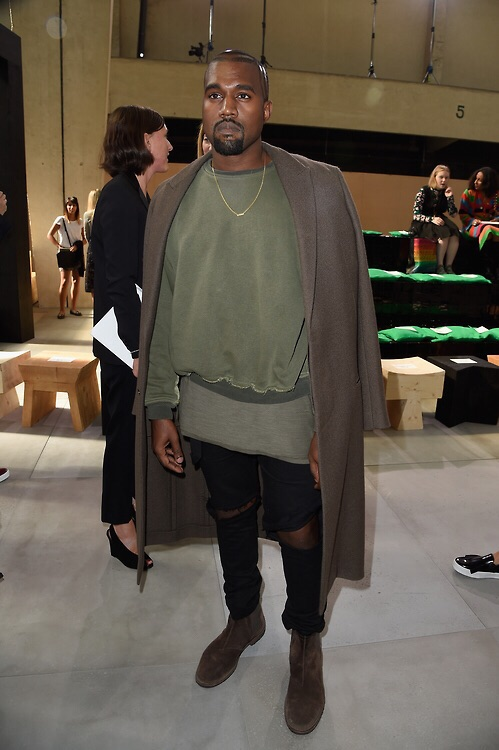Kanye West at the Celine show. Wearing Haider Ackermann sweatshirt, Botegga Veneta Chelsea boots , Yeezustourmerch and Overcoat.