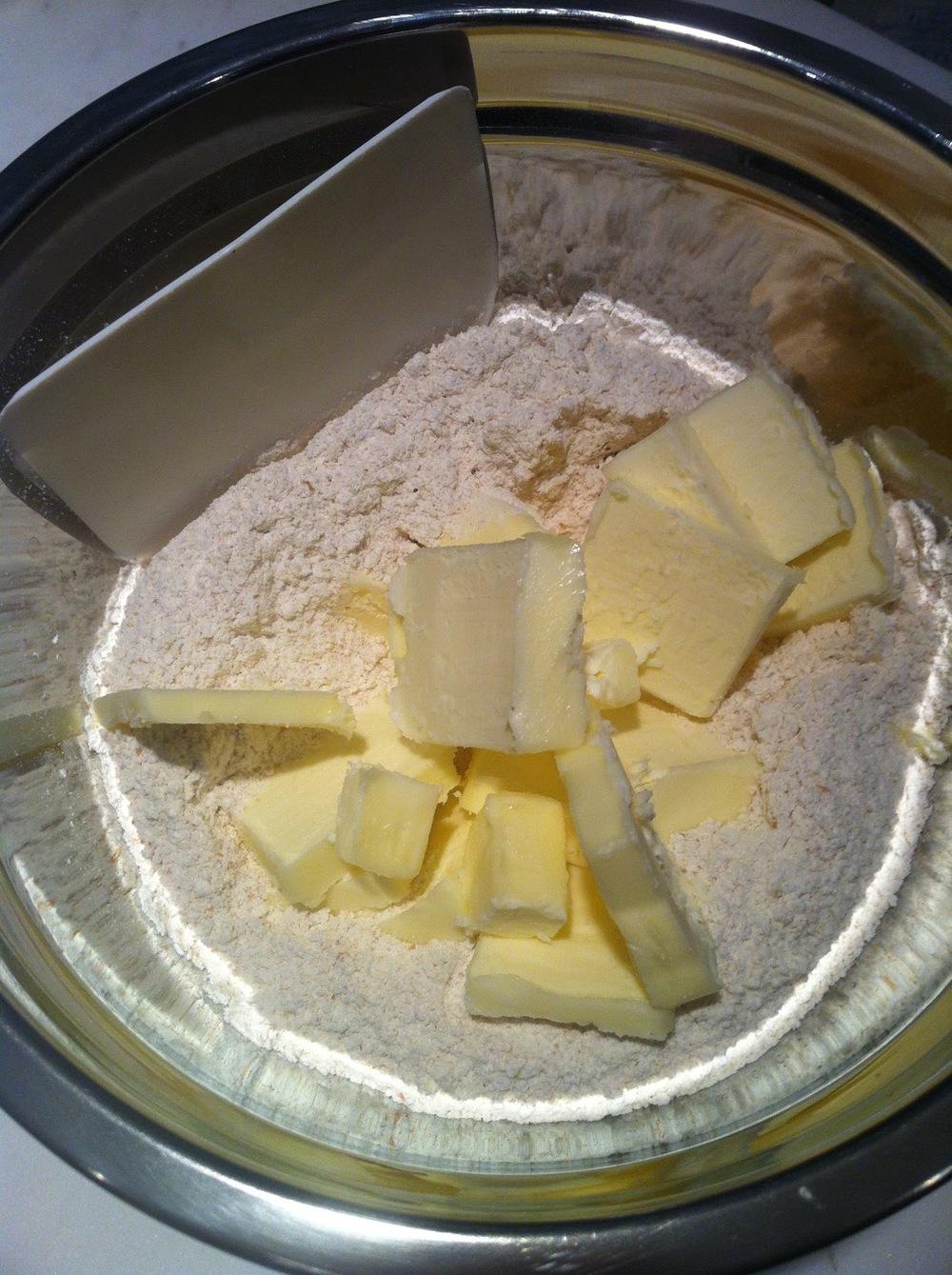 Misture os ingredientes secos numa tigela grande e alta. Corte os tabletes de manteiga em pedaços pequenos e junte-os aos secos.