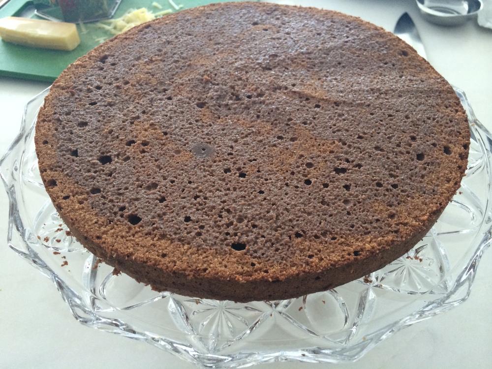 Coloque a parte de cima do bolo virada pra baixo e umedeça esta primeira camada de bolo com metade da mistura de cacau e leite. Utilize um pincel de silicone ou uma colher pra fazer isto.