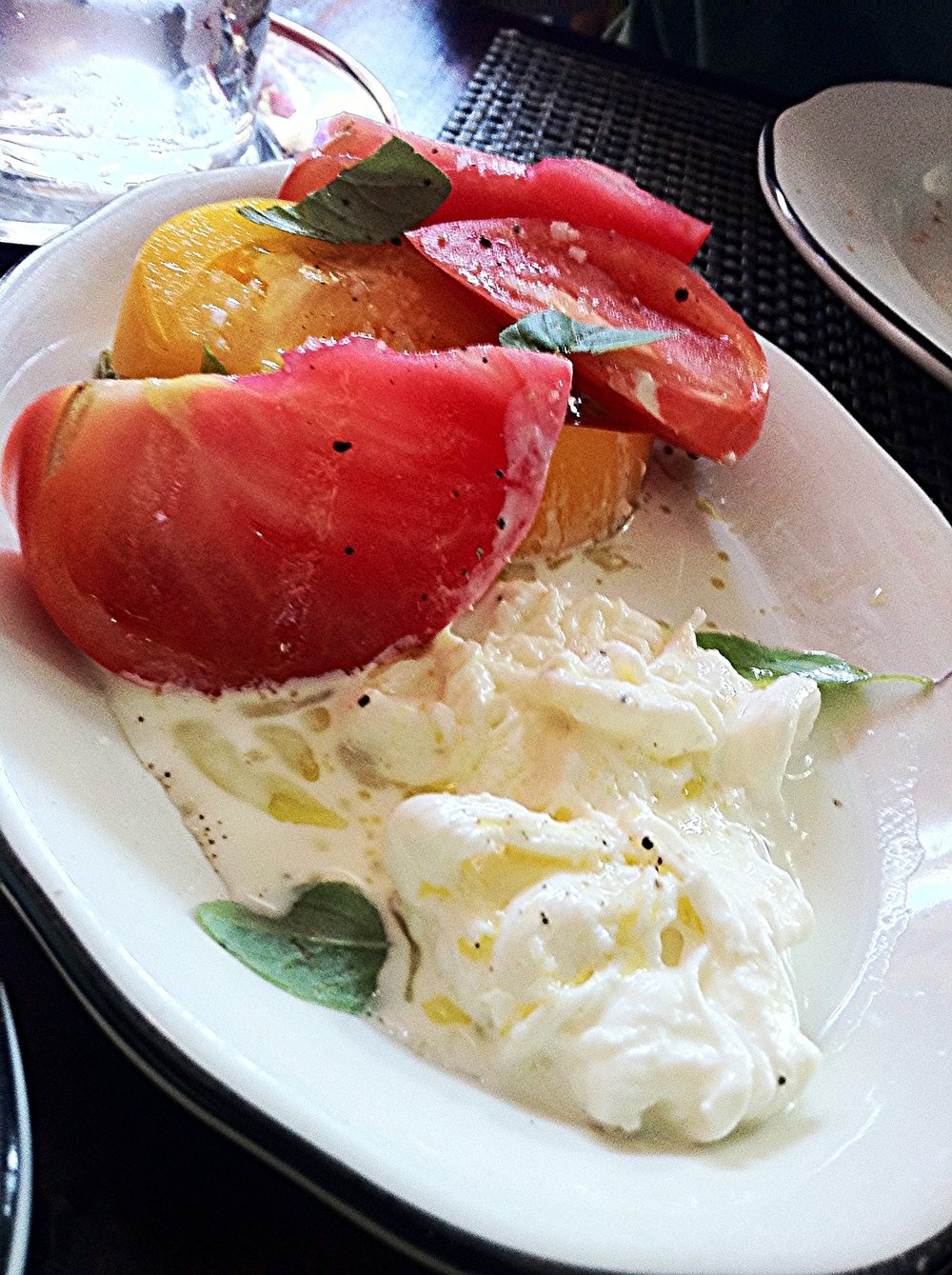Os deliciosos  Heirloom Tomatoes  com queijo  Stracciatella , azeite, manjericão, flor de sal e pimenta.