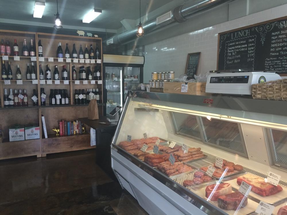 O refrigerador de carnes e embutidos, com a adega de vinhos inusitados ao fundo. Em frente ao balcão refrigerado há uma geladeira com vários rótulos de cervejas bem interessantes.