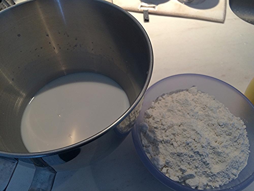 Dissolva o açúcar, o fermento e o leite em pó na água. Misture os demais ingredientes secos à metade da farinha.Acrescente 500g de farinha e leve pra bater na batedeira em velocidade baixa, até incorporar. Acrescente mais 250g de farinha de trigo à massa, que ainda estará muito mole e pegajosa. Aguarde incorporar. Adicione mais 100g e verifique a textura. Eu não precisei usar os 150g restantes aqui, mas usei um pouco da farinha na hora de abrir. acredito que minha massa ficou boa com 900g de farinha*. Adicione a manteiga em pedaços pequenos, até que se dissolvam na massa.