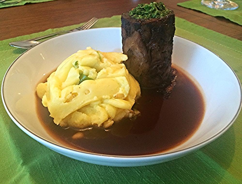 Cordeiro cozido longamente no vinho Malbec, servido no próprio molho de cocção e acompanhado de purê de batatas com pinholi e rúcula.