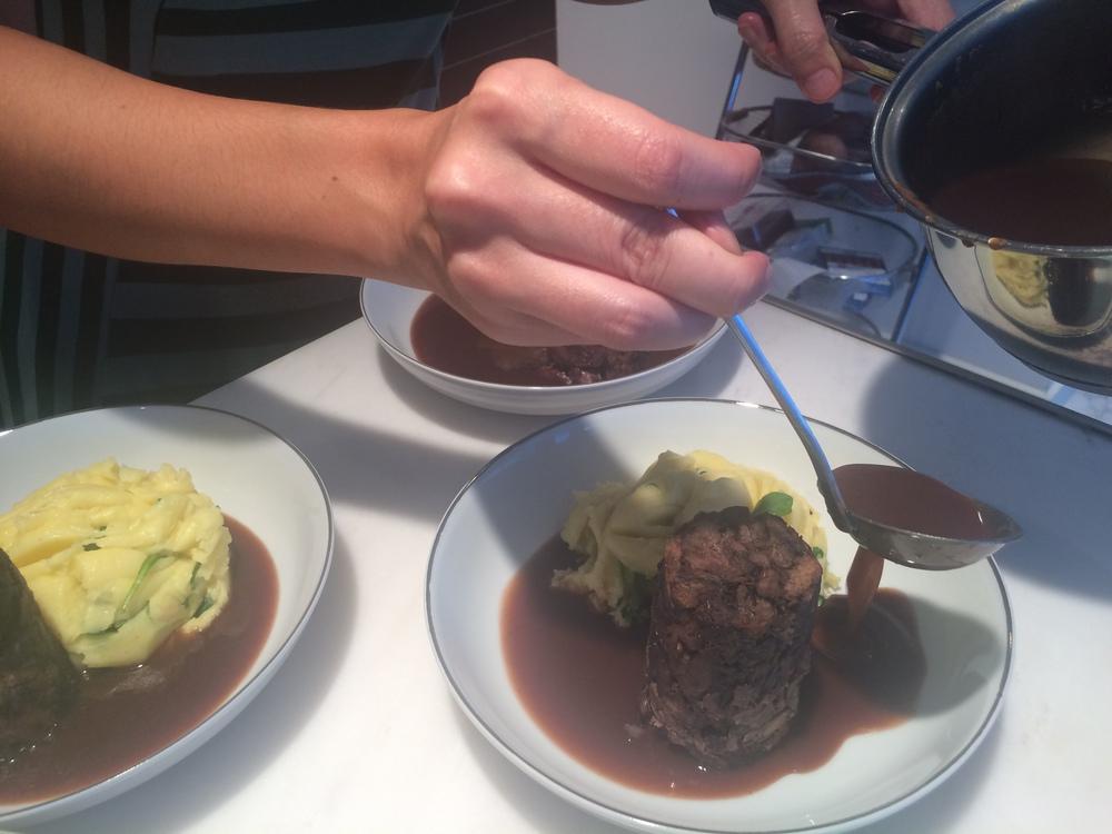 Monte os pratos primeiro com o purê, segundo com o medalhão e terceiro com o caldo, até cobrir a parte funda e branca do prato. Repare no tanto que o molho está viscoso. Delícia!