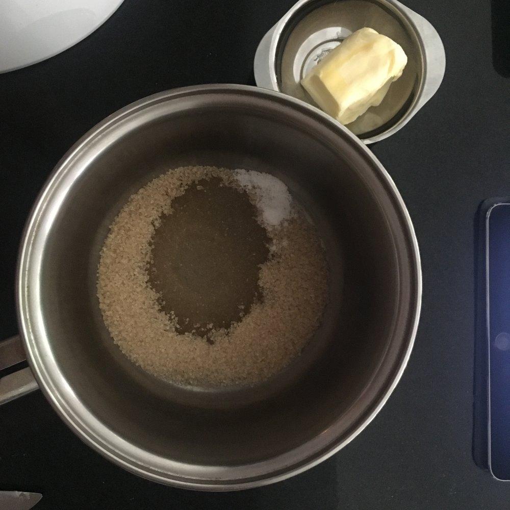 Enquanto esfria o bolo, faça a cobertura: leve o açúcar, a manteiga e a água ao fogo. Assim que a manteiga derreter inteiramente, conte 3 minutos em fogo baixo.