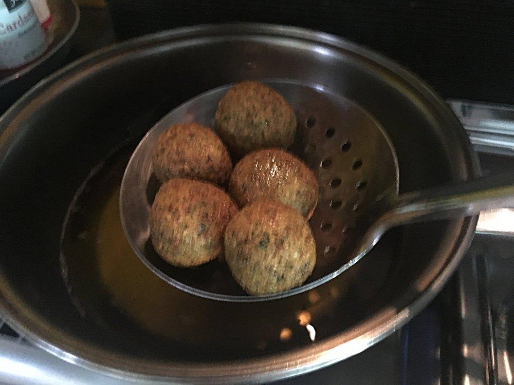 Frite por imersão em óleo não muito quente. Frite em etapas, não encha muito a panela de óleo. E não mexa nos bolinhos imediatamente depois de colocá-los no óleo quente. Lembre-se de que a massa é muito frágil e é preciso formar uma crosta neles antes de movê-los. Quando estiver dourado por fora, retire e seque num papel de pão ou papel toalha.