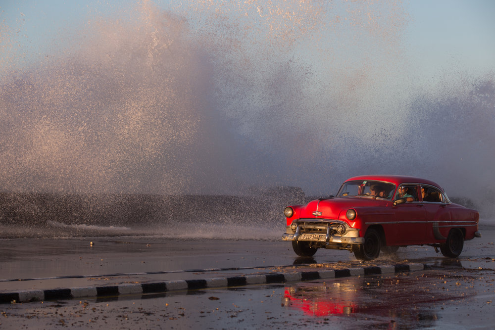 1950's Chevrolet taxi drives down Havana's Malecón as waves crash over the sea wall.