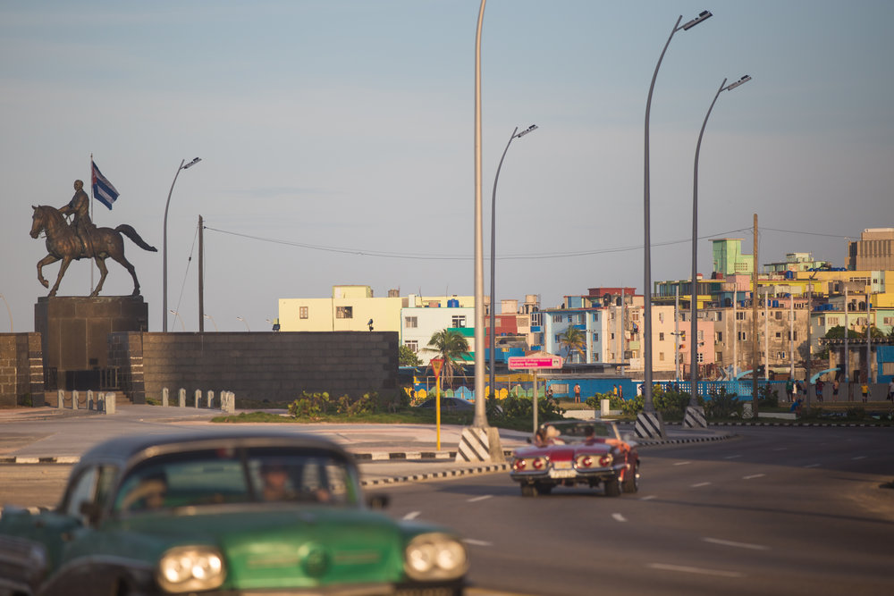 Classic American cars drive along Havana's Malecón, passing the Cuban flag and statue of Calixto Garcia on horseback - a general for the Cuban War for Independence.