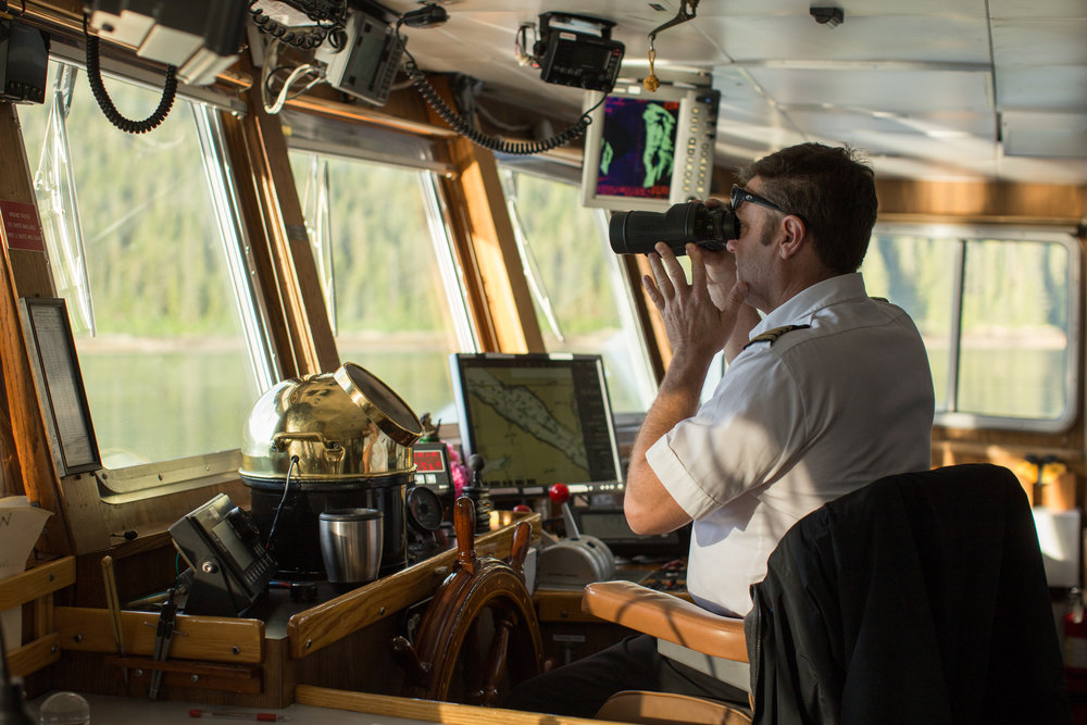 Captain of the Sea Lion looks through binoculars in the ship's bridge.