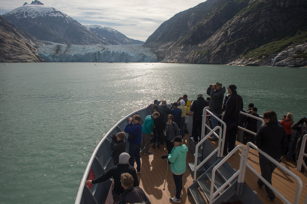Guests on bow of Sea Lion ship viewing Dawes Glacier.