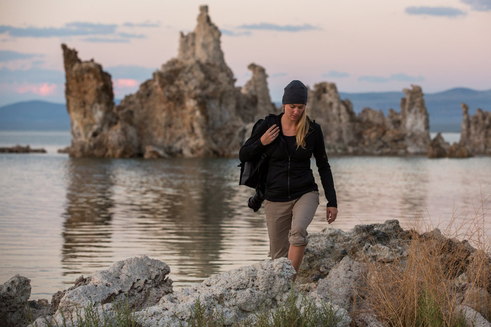 Young woman hikes with a camera at South Lake Tufa Area, Mono Lake, California.