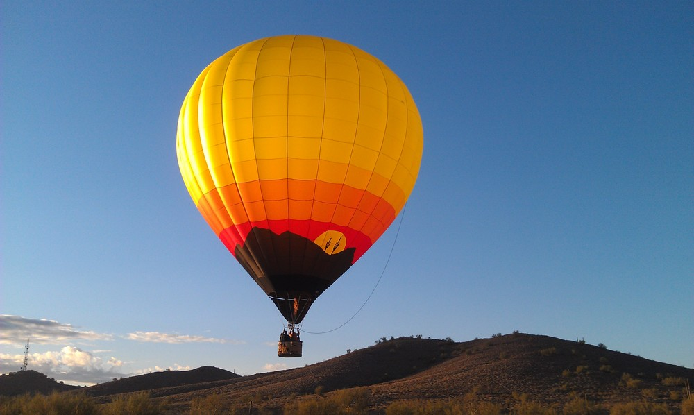 A hot air balloon flight nearing it's landing spot.