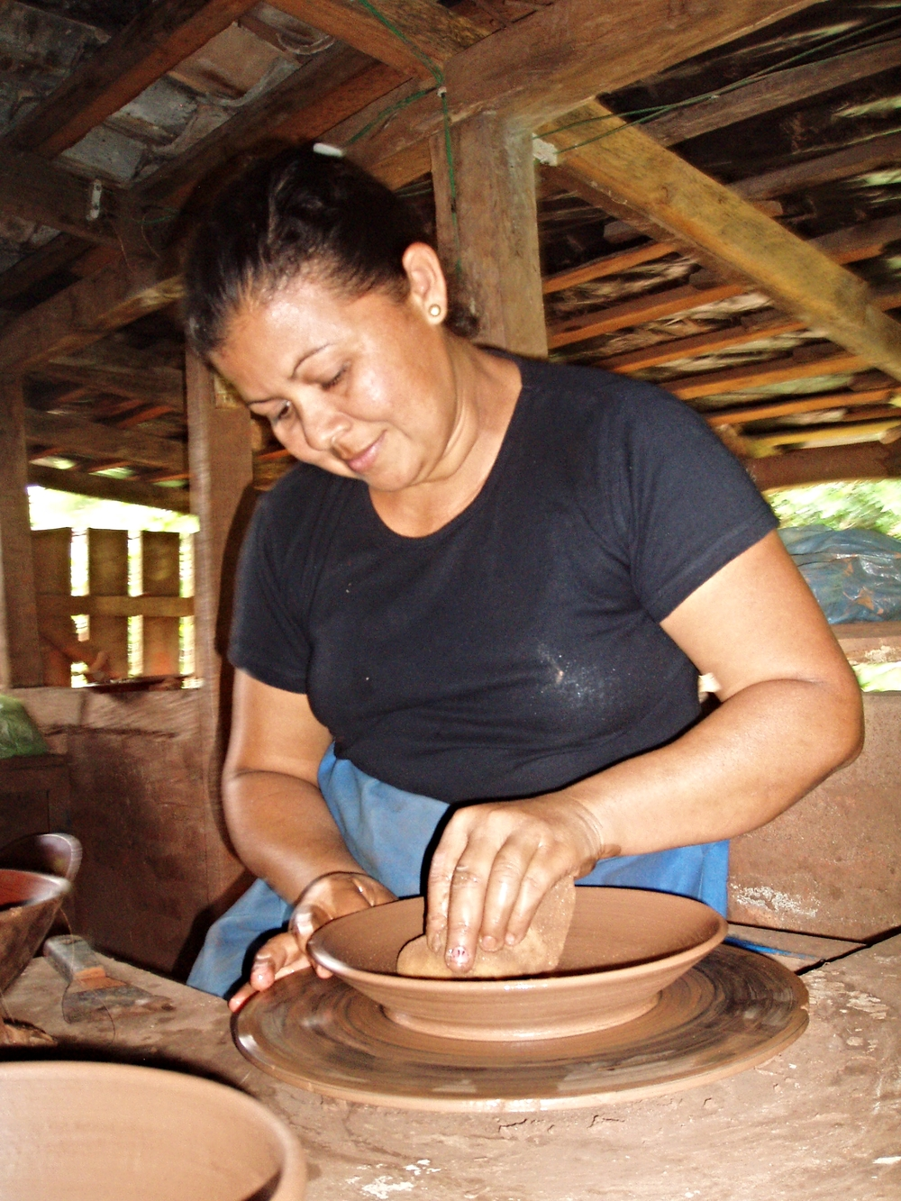Plates and bowls are a popular export. Here, a sculptor smoothes the clay on a pottery wheel—the   first step of many.