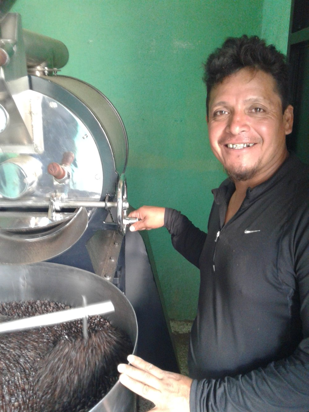 Pictured: Victor using the coffee roaster SGDF helped him purchase.
