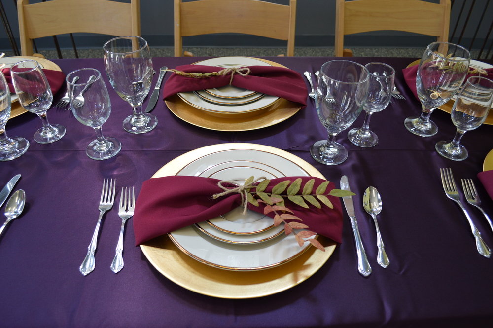 Displayed: Gold Rimmed China, Gold Charger, Flatware, 16 oz. Water Goblet, Wine Glass, Burgundy Napkin, Eggplant Linen, and Flatware