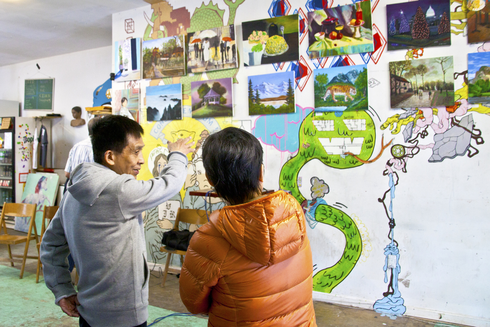 Mr. Xing Yi Tian and Ms. Bei Yu admiring art painted by themselves and by thier friends from the Senior Center. From the Silent Barn – Diana Jones Center joint event, Landscaping for Links. Photo Credit MF Clarke