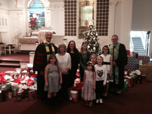Christmas in November 2015 Pictured are Pastors Galen and Fred, along with representatives from area nursing facilities and children of the church, and surrounded by gifts from the congregation for residents of Manor Care, Elizabethtown Nursing Facility, and Susquehanna Nursing Facility.
