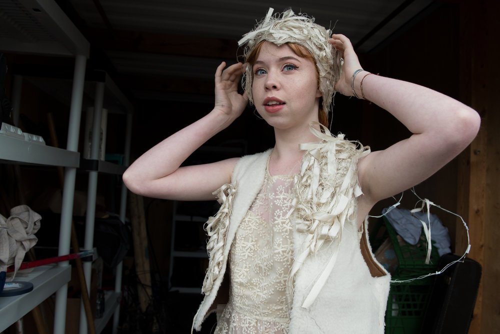 Behind the scenes, Katie Duncan fixes her hairpiece inside a shipping container in the parking lot as she transforms into Mustardseed. Duncan, a theatre student at Emerson College, is one of many actors participating in this year's Shakespeare production.
