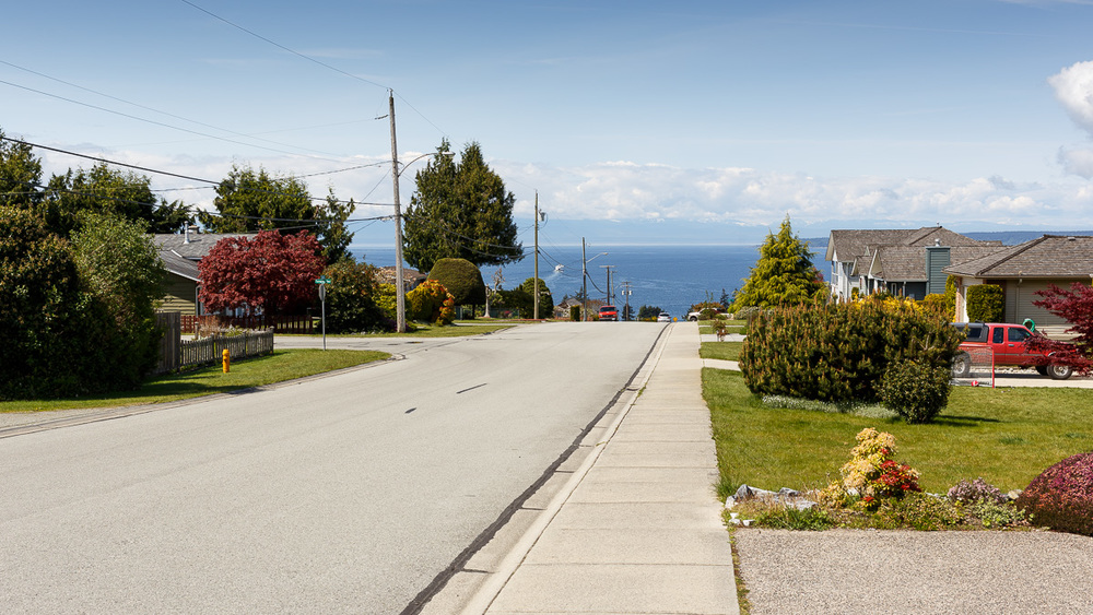 The town is on a hillside, with streets dropping down to the ocean. Vancouver Island is visible in the distance.