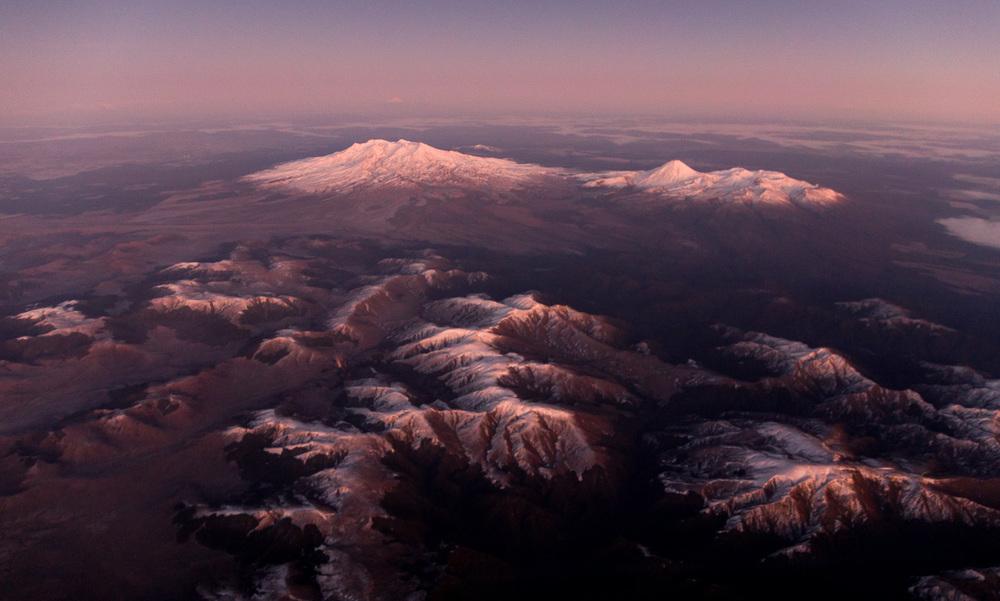The Kaimanawa Ranges and Mount Ruapehu, Ngauruhoe and Tongariro, illuminated pink in pre dawn light.