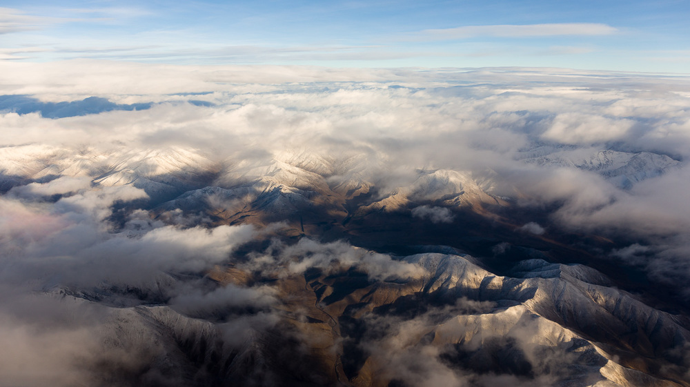 Snow covered ranges peak through the clouds, South Island.