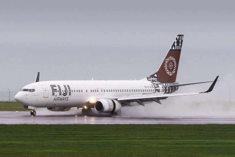 Fiji Airways Boeing 737-800 DQ-FJG arriving on a wet runway 05R at Auckland. June 2016.