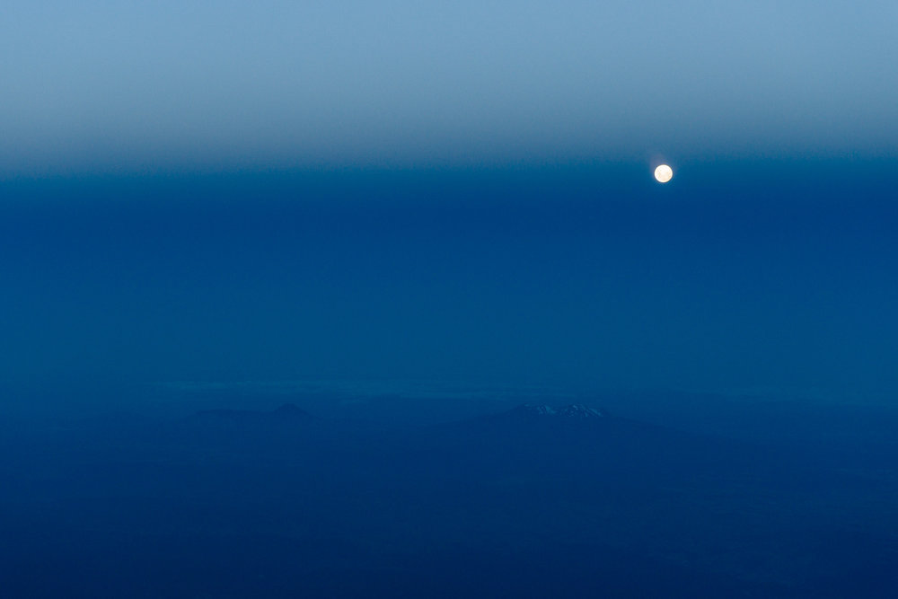 The full moon rising trough the edgge of the umbra, with Mount Ruapehu and Mount Ngauruhoe beneath.