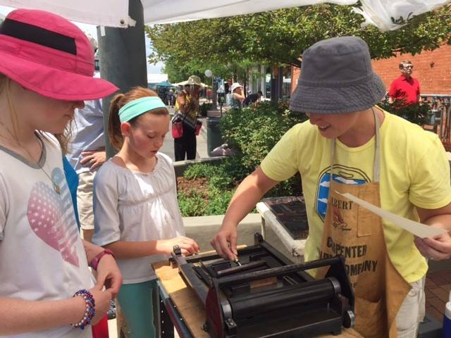 Elanor demonstrating inking on the proof press at the Cherry Creek Arts Festival