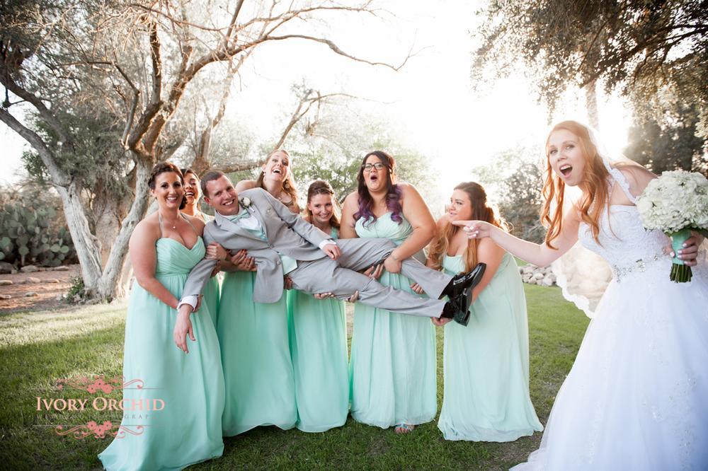 bridesmaids holding groom