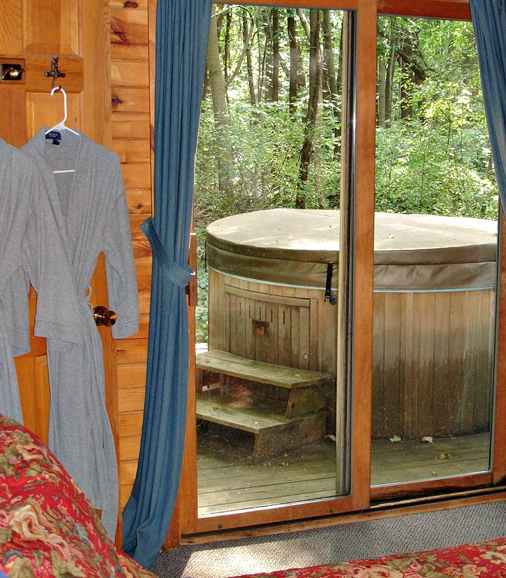 Bedroom in Bill's Cabin with view of private outdoor hot tub in background