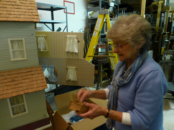 LCHS board member Terry Visger removes dollhouse furnishings so they won't get damaged