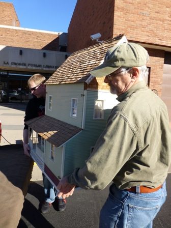 LCHS volunteers Kevin Vach and Bob Mullen transporting a doll house to its new home