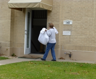 Volunteer and Board Member Lynn Harlan carries textiles into the new location to be hung up.
