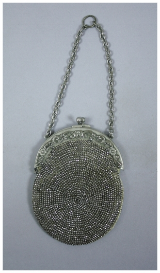 c. 1900  A small beaded purse. The steel cut beads are in a circular pattern and are crocheted on. There is a metal frame and chain, which is probably German silver. It clamps shut. The purse is lined with suede. The beads are rusted.