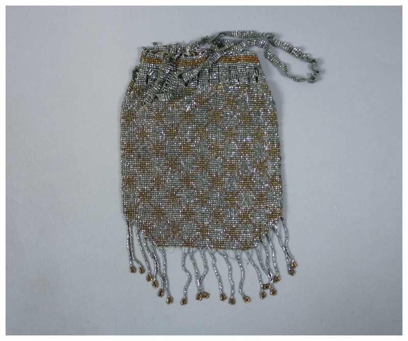 Faceted metal bead purse in silver with copper snowflake design. There is an interwoven bead closure and tassels at the bottom.