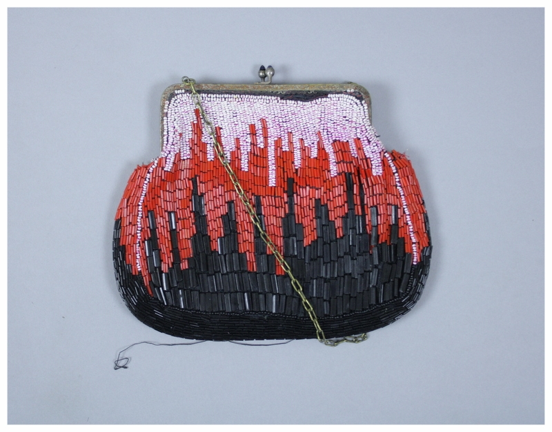 A small beaded purse with a metal frame and chain. The beads are black, red, and an off white/pink color. It is in an art deco pattern. The inside has black lining and a small pouch inside.