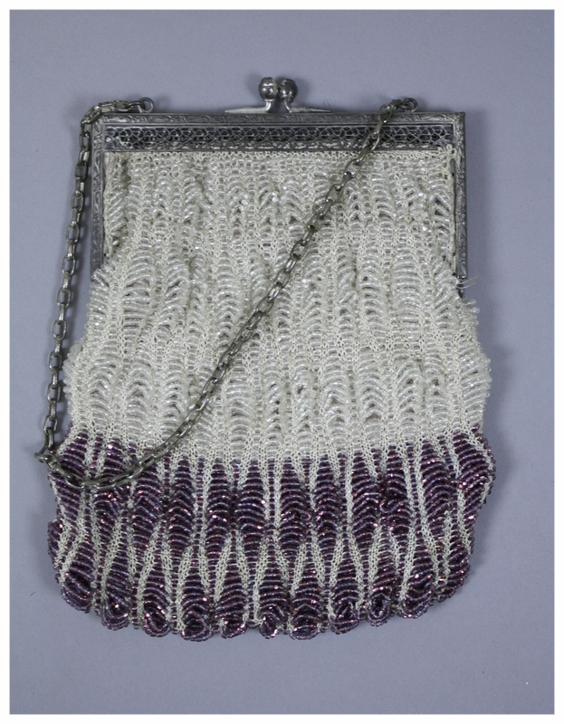 A purple and clear beaded purse. Purse has a crocheted underlayer of white with the purple and clear beads sewn on. The frame is made of silver medal with a floral design and silver metal clasps. Interior of purse is lined with pink sateen. Bag does appear to be sewn together by hand.