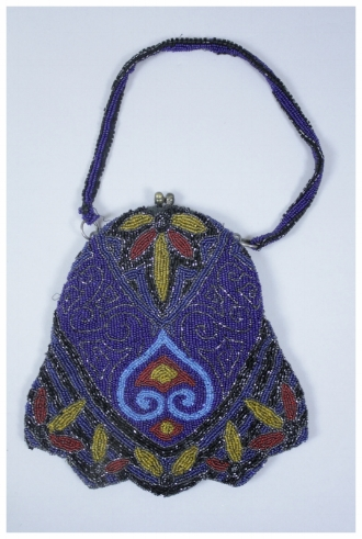 A blue beaded purse with different shades of blue, red, gold, and black. Some of the beads are round and regular. Other beads are faceted and irregular. There is a metal frame and gold colored clasp. Beaded handle of navy and black beads on both sides. Interior is lined with pink silk. Small glass mirror was found inside the purse.