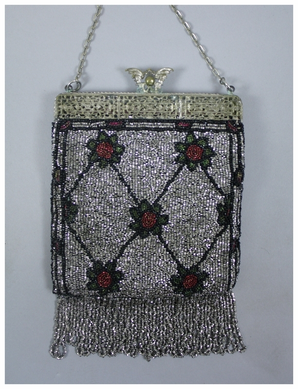 A beaded purse with fringe. It is silver, but also has green and red flowers with black outlines. The flowers are connected with diagonal lines. The fringe on bottom is composed of silver beads. It has an ornate silver frame and chain. The inside is lined with pink fabric and has a small, pink covered mirror attached.