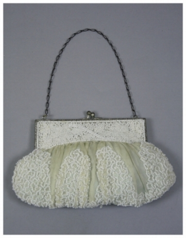 A beaded bag with white seed beads in a looped pattern on white chiffon. There is a metal frame with a chain handle. It has a blue taffeta lining.