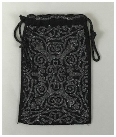 c. 1890  A black and silver beaded drawstring purse that is a reticule. Drawstrings are black cord. There is a matching geometrical pattern on both sides.