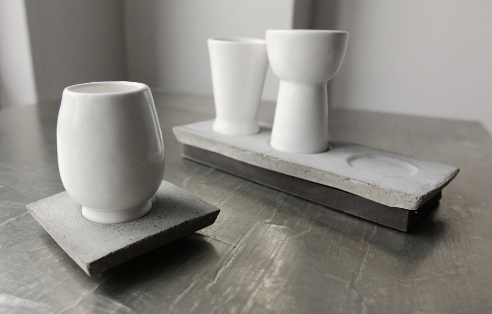 Tea cups made of porcelain and saucers made of cast concrete and ebony wood