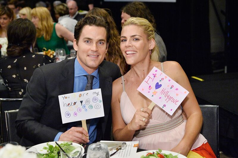 Matt Bomer  and  Busy Philipps  raise their auction paddles during  Uplift Family Services at Hollygrove Gala. Photo Credit:  Stefanie Keenan/Getty Images