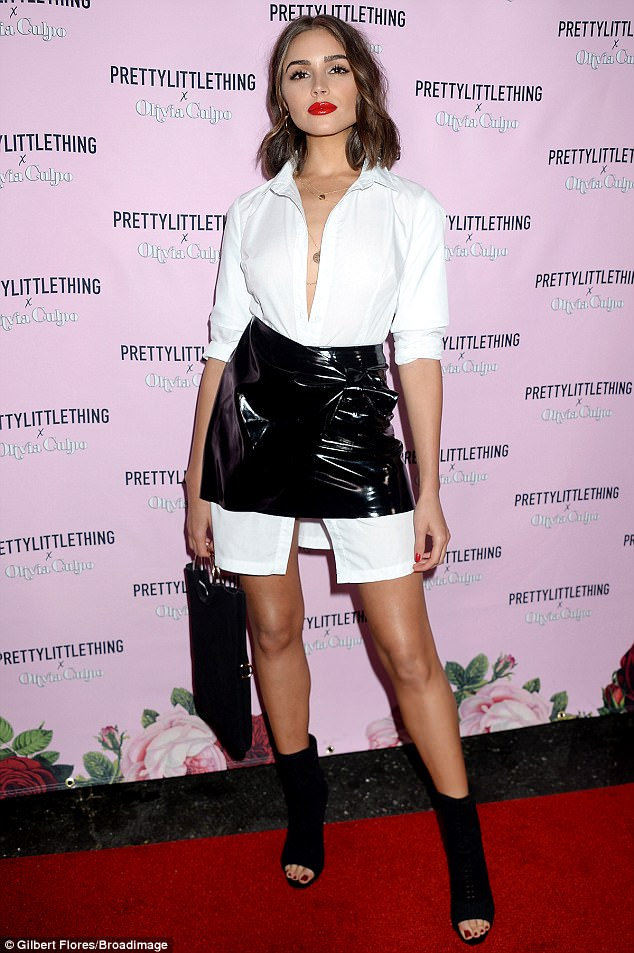 Olivia Culpo wearing pieces from her recent collab with PLT. Photo Courtesy of BroadImage Get The Look Yourself:   BLACK VINYL BOW WRAP MINI SKIRT    $44.00 &    WHITE DOUBLE CUFF TIE WAIST SHIRT DRESS    $55.00