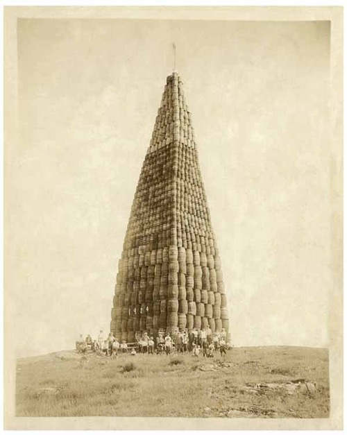 An image from Folk Object depicting a tower of barrels to be burned for Prohibition in 1924