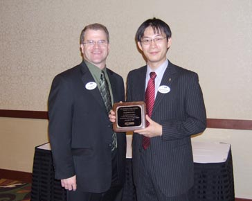 NCI Director Brian Sorenson presents a plaque to Kenji Motomatsu, Nisshin Flour Milling Company, Japan, in appreciation of the work Kenji did in the swing mill before its opening.